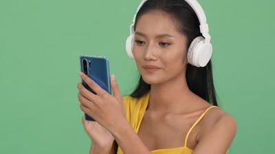 Woman wearing headphone and hold smartphone