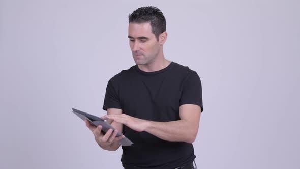 Thumbnail for Glücklicher gutaussehender Mann mit digitalem Tablet und immer gute Nachrichten