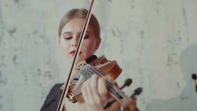 Admiring Female Musician Playing the Violin Emotionally at Camera
