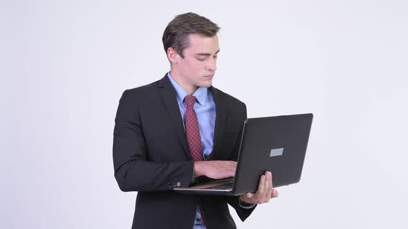 Thumbnail for Young Happy Handsome Businessman Using Laptop