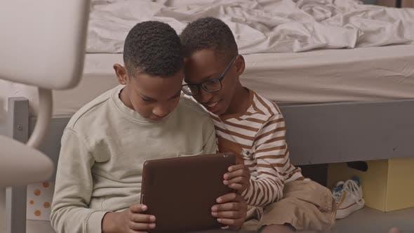 African American Twin Boys Using Digital Tablet