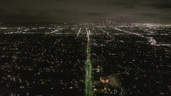 Thumbnail for AERIAL: View Over Los Angeles at Night with Wilshire Boulevard Glowing Streets and City Car Traffic