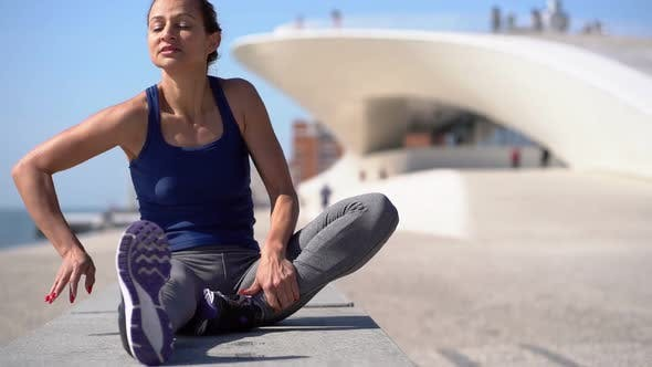 Thumbnail for Athletic Focused Girl Sitting and Stretching Legs at Riverside