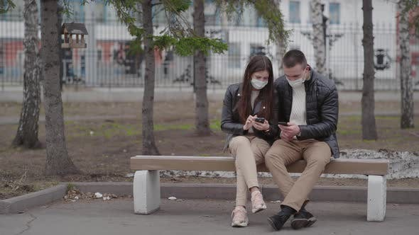 Thumbnail for A Man and a Woman Wear Protective Masks on the Street Online Using a Smartphone During the Pandemic