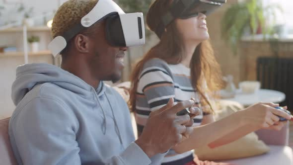 Cheerful Couple Playing Video Game on VR Headsets