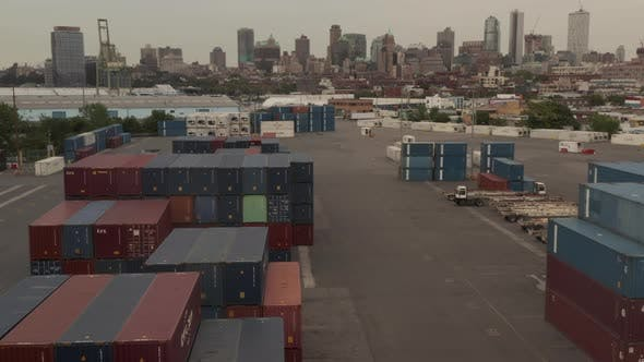 Flying Over Red and Blue Industrial Cargo Containers in Docks with New York City with