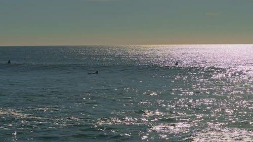 People swimming in the Atlantic Ocean at sunset