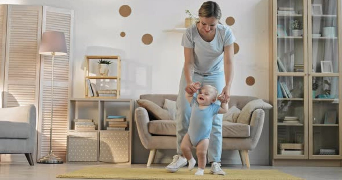 Baby Boy Making First Steps with Mother Help