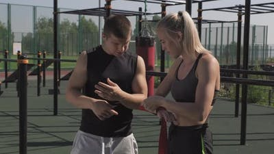 Girl Bandaging Hands With Hand Wraps At Boxing Training