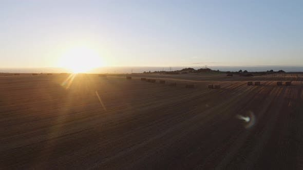 Wide Angle View of Vast Piece of Farming Land and Sun Setting Low in Background
