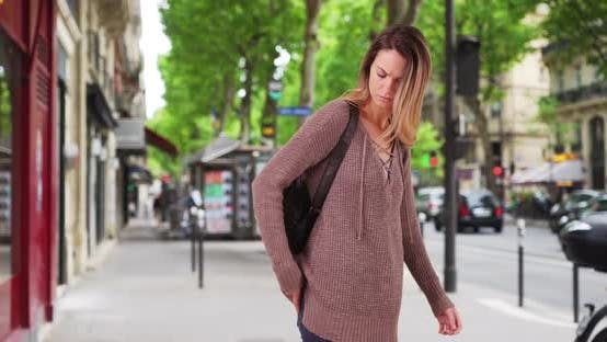 Thumbnail for Pretty Caucasian woman walks down the street using smartphone for directions