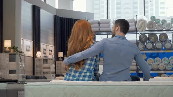 Thumbnail for Rear View Shot of a Couple Hugging Sitting on a New Bed at Furniture Store