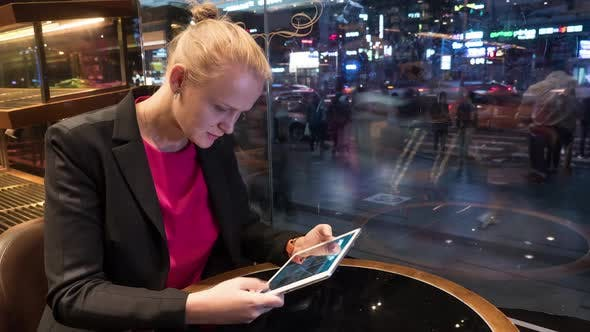 Thumbnail for Woman Using Pad in Cafe By Window with City View