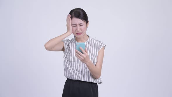 Thumbnail for Stressed Asian Businesswoman Using Phone and Getting Bad News