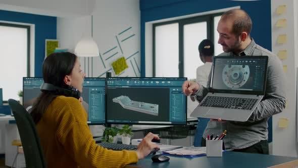 Ingenieur hält Laptop und zeigt auf dem Display