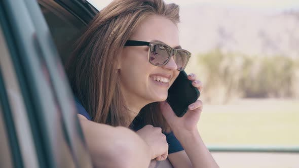 Thumbnail for Smiling Lady with Phone Looks Out of Open Automobile Window