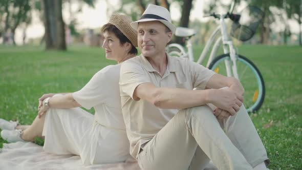 Cheerful Mid-adult Man and Woman Sitting Back To Back on Green Lawn and Talking