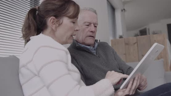 Senior adult couple at home on sofa looking at digital tablet