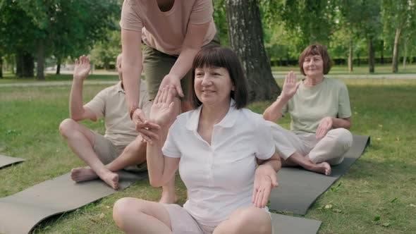 Three Seniors Practicing Yoga with Coach Help