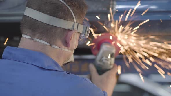 Thumbnail for Back View Close-up of Male Caucasian Worker Using Metal Grinder. Professional Man Working in Auto