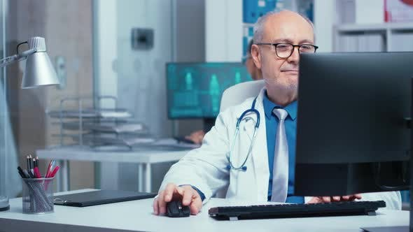 Thumbnail for Elderly Doctor Working on PC