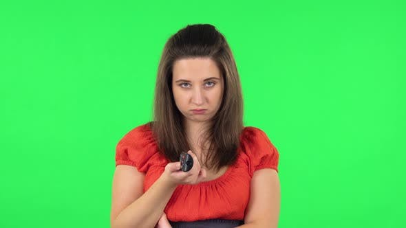 Thumbnail for Portrait of Cute Girl with TV Remote in Her Hands, Switching on TV. Green Screen