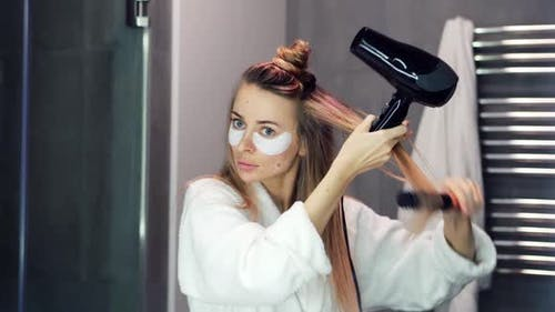 Woman with Eye Patches Drying Her Hair with Hair Dryer and Brush