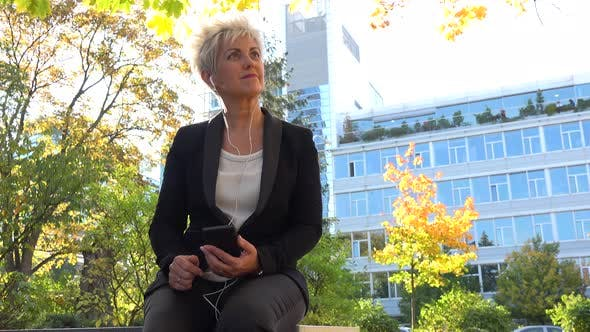 Thumbnail for A Middle-aged Businesswoman Sits on a Bench in a Park and Listens To Music on a Smartphone