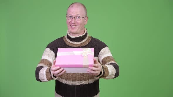 Thumbnail for Happy Mature Bald Man Smiling While Giving Gift Box