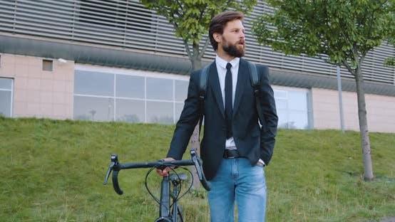 Bärtiger Mann in dunkler Jacke und Jeans, die mit seinem Fahrrad auf der Straße geht