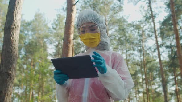 Thumbnail for Female Scientist in Protective Suit Working on Tablet Pc