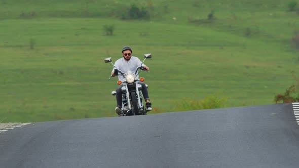 Thumbnail for Man riding a motorcycle on a rural road