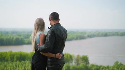 Blonde Woman and Motorcyclist Hug Looking at River