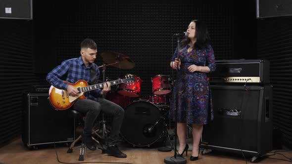 Guitarist and female singer are performing live concert