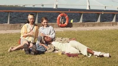 Multiethnic Girlfriends Resting on Embankment