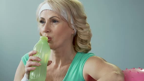Thumbnail for Lady of Senior Age Leaning on Fitness Ball, Drinking Water and Exhaling, Results