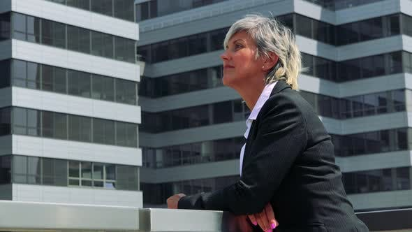 Thumbnail for Business Middle Age Woman Looks Around - Company Building in the Background - Closeup