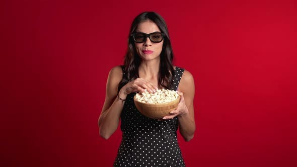 Thumbnail for Young Hispanic Woman in 3d Glasses Watching Comedy Movie, Eating Popcorn on Red