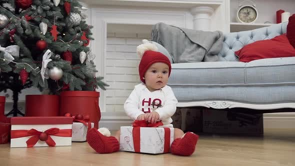 Thumbnail for Cute Little Baby Dressed in Christmas Clothes Sitting with a Present Between the Christmas Tree