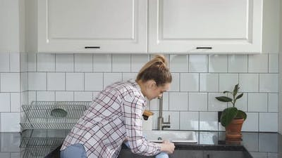 Young Woman Washes Cleaning Kitchen Set with Rag or Cloth