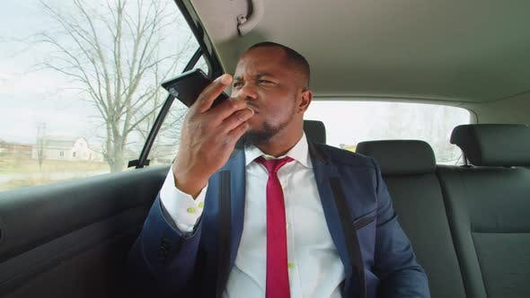 Strict Black Entrepreneur Making Voice Call Conference in Vehicle