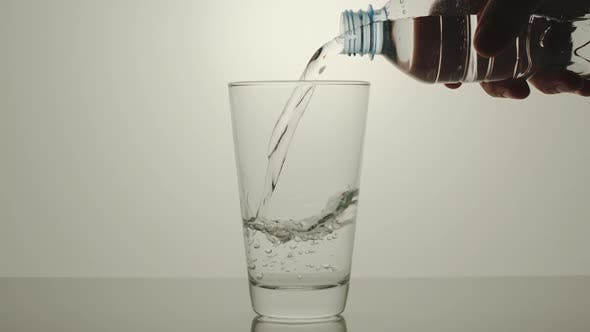 Thumbnail for Hand pouring pure water from a plastic bottle into a glass
