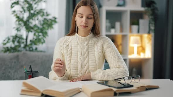 Woman in Earphones Studying at Table
