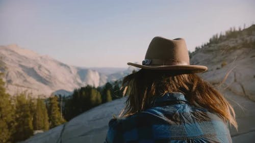 Back View of Young Tourist Girl Sitting Alone on a Rock Watching Mountain View at Yosemite
