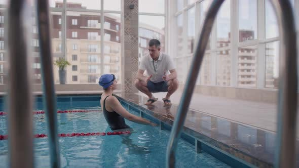 Female Swimmer Receiving Advice from Coach