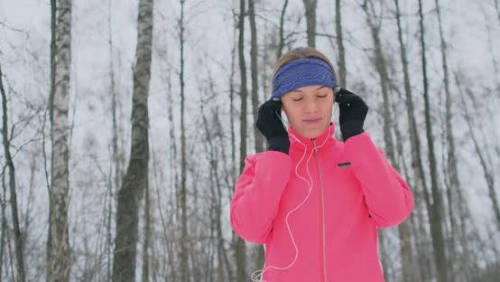 Cover Image for The Girl Before the Morning Winter Jog Inserts Headphones in the Ears and Is Preparing To Run