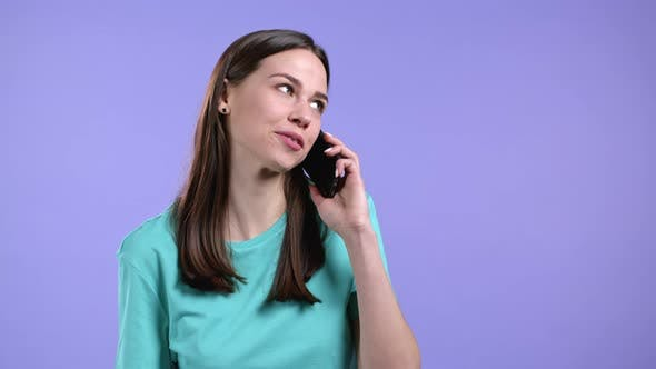 Young Woman Speaks with Smile on Phone