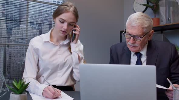 Senior Businessman Company Director Working on Laptop Computer in Office Secretary Talking on Phone