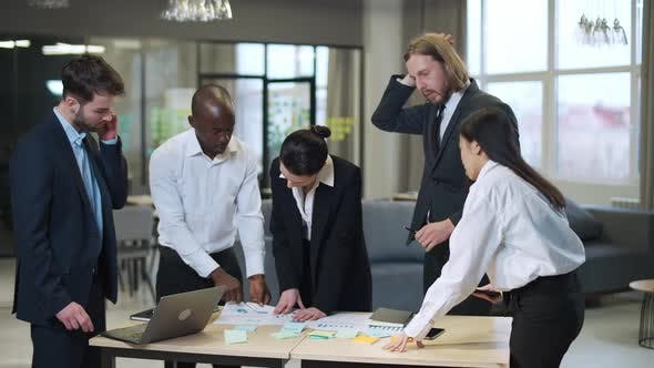 Business Meeting International Management Team at Work Team Is Standing Next To a Work Table and