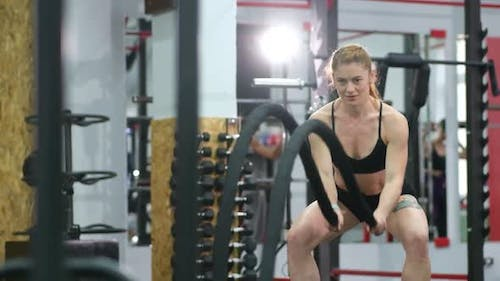 Young woman doing some crossfit exercises with a rope
